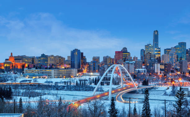 Edmonton Downtown Skyline Just After Sunset in the Winter Edmonton downtown Winter skyline just after sunset showing Alberta Legislature and Walterdale Bridge across the frozen, snow-covered Saskatchewan River and surrounding skyscrapers. Edmonton is the capital of Alberta, Canada. alberta stock pictures, royalty-free photos & images