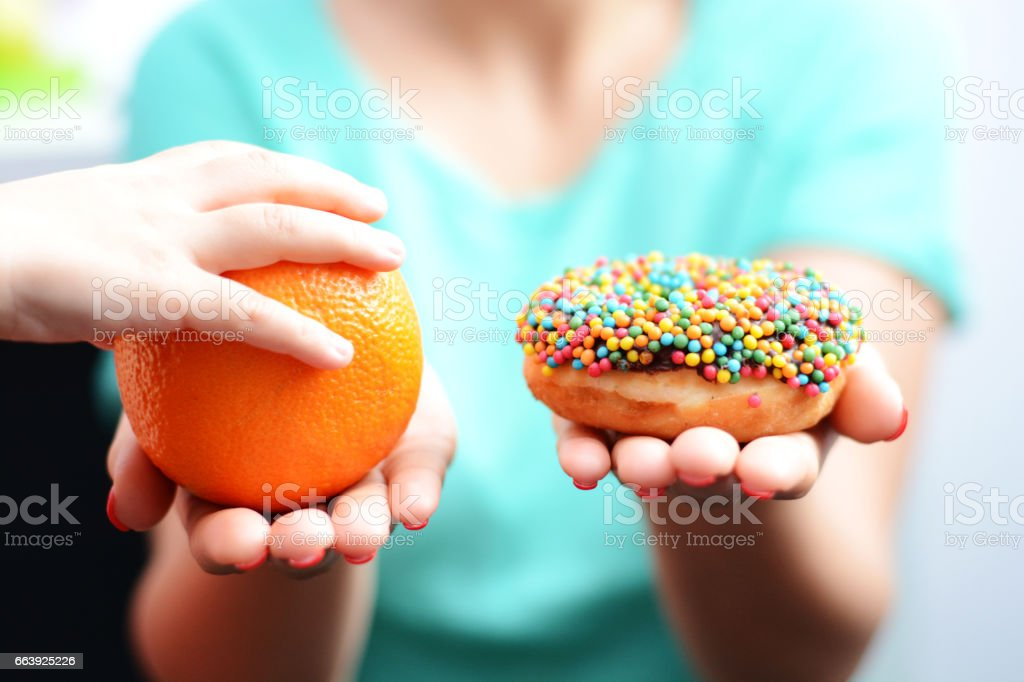 Educate children to choose healthy food concept with little girl choice to eat fruit, not a donut stock photo