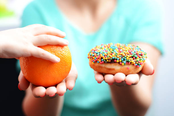 educate children to choose healthy food concept with little girl choice to eat fruit, not a donut - zuckerfreie lebensmittel stock-fotos und bilder