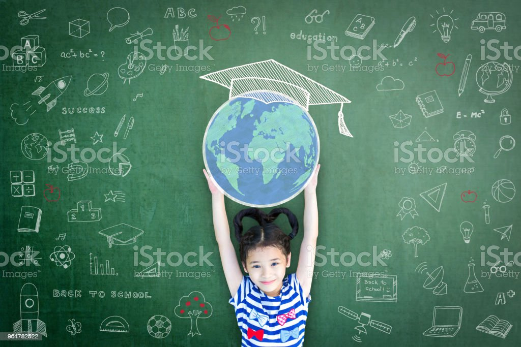 Educated school child girl lifting world globe doodle on chalkboard for children's education international children day and world literacy day concept royalty-free stock photo