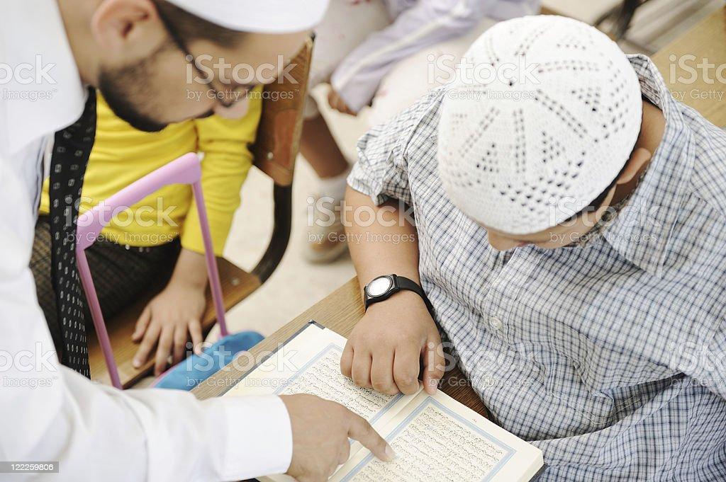 Education activities in classroom, Muslim teacher showing Koran to kid stock photo