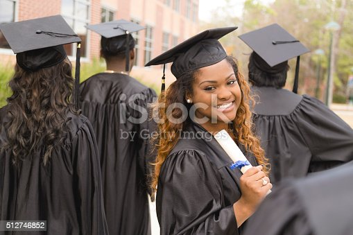 istock Education: African descent female graduate and friends on college campus. 512746852