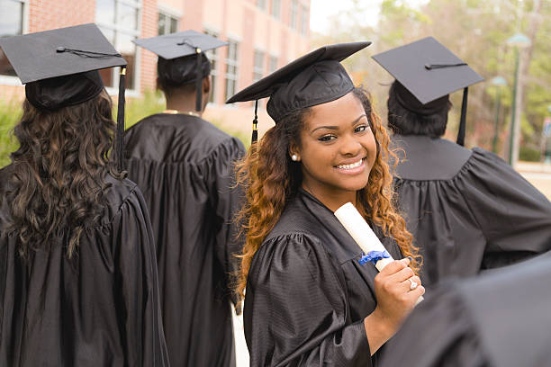 Education: African descent female graduate and friends on college campus. stock photo