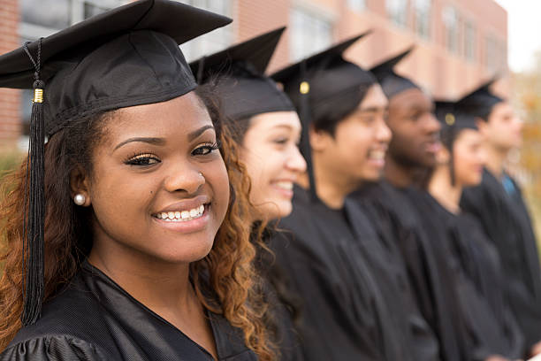 Education: African descent graduate and friends on college campus. stock photo