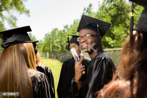 istock Education: African descent graduate holds diploma after graduation. Friends. 481998677