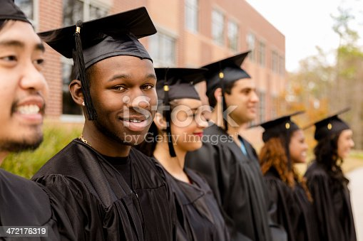 istock Education: African descent male graduate and friends on college campus. 472176319