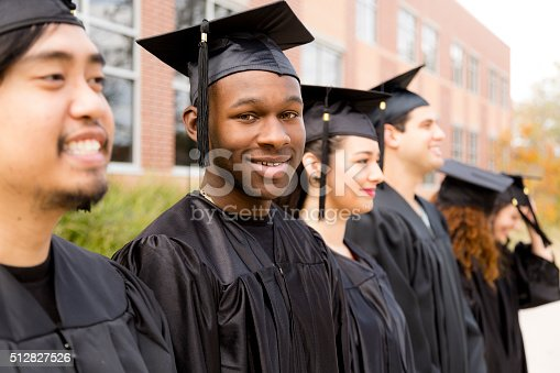 istock Education: African descent male graduate and friends on college campus. 512827526