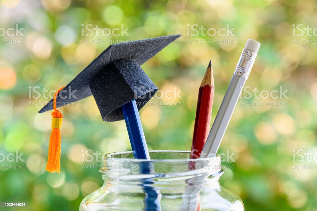Education and knowledge is important for student and most powerful weapon concept : Black graduation cap or hat on pencil in bottle, depicts the power of success in education. Green nature background. stock photo