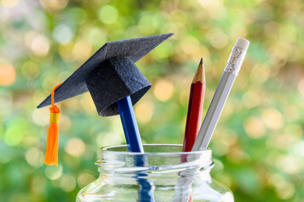 education and knowledge is important for student and most powerful weapon concept : black graduation cap or hat on pencil in bottle, depicts the power of success in education. green nature background. - reunion stock photos and pictures