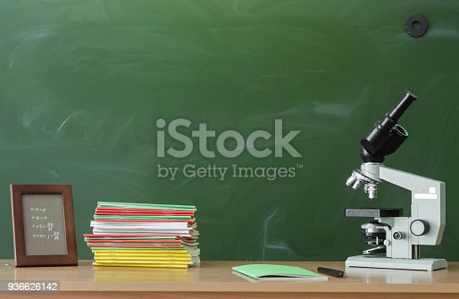 istock Education background with copy space. Student or teacher desk table on blackboard background. Classroom. Back to school. 936626142