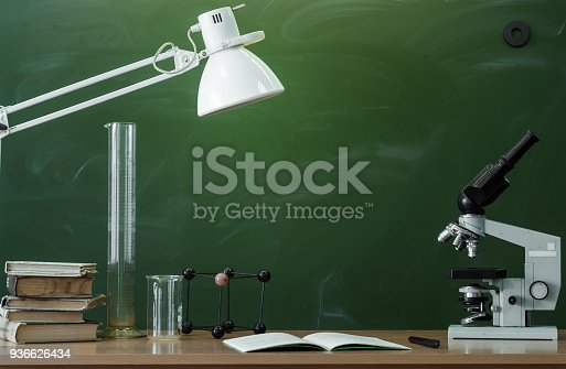 istock Education background with copy space. Student or teacher desk table on blackboard background. Classroom. Back to school. 936626434