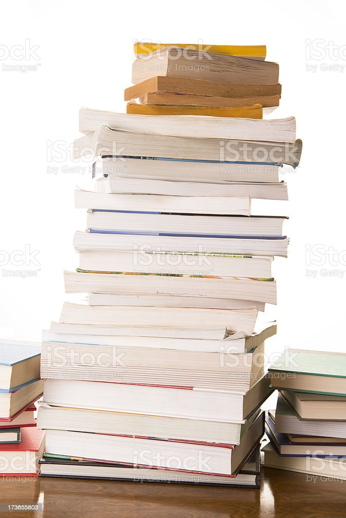 Education: Books stacked high on library table paperback and hardback royalty-free stock photo