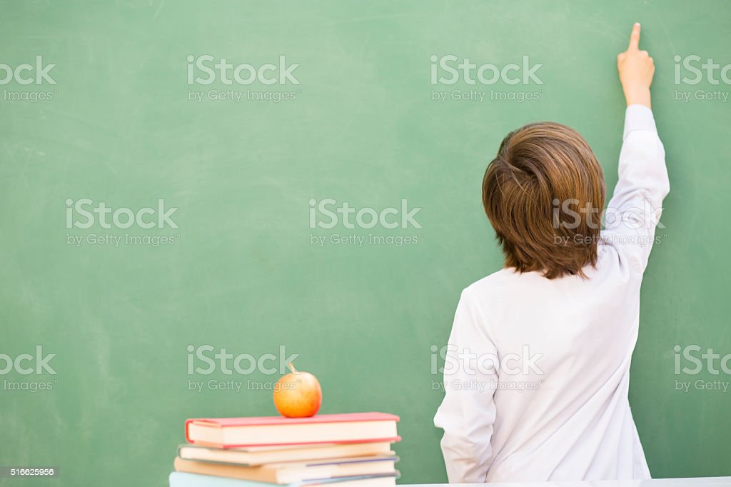 Rear view of little boy wearing lab coat pointing up on a green...
