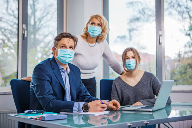 Education classroom setting with a beautiful blonde teacher and a family during the Covid-19 pandemic Education classroom setting with a beautiful blonde female teacher wearing protective face mask and respecting social distancing during the Covid-19 pandemic teacher appreciation week stock pictures, royalty-free photos & images