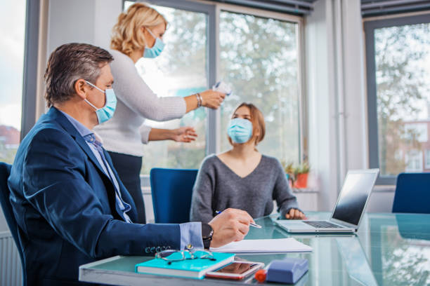 Education classroom setting with for a beautiful blonde teacher during the Covid-19 pandemic Education classroom setting with a beautiful blonde female teacher wearing protective face mask and respecting social distancing during the Covid-19 pandemic teacher appreciation week stock pictures, royalty-free photos & images