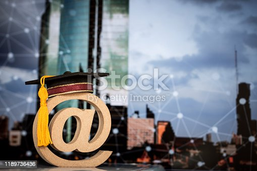 istock Education Communication in abroad international concept: Graduation cap on wood email address symbol on blur city network background. Idea success for in university of learning can learn everywhere 1189736436