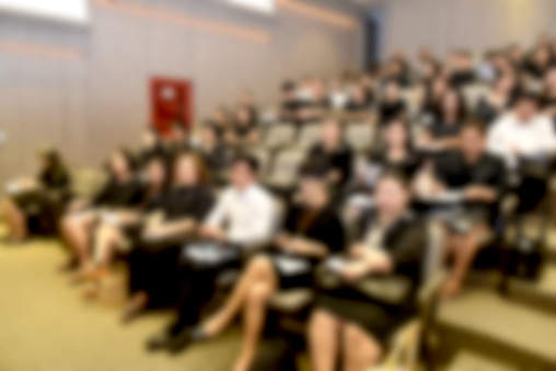 831720990 istock photo Education concept. Abstract blurred background image of education people, business people and students sitting in conference room or large hall with screen and projector for showing information. 814311150