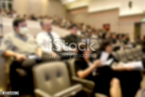 831720990istockphoto Education concept. Abstract blurred background image of education people, business people and students sitting in conference room or large hall with screen and projector for showing information. 814312290