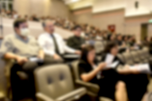 831720990 istock photo Education concept. Abstract blurred background image of education people, business people and students sitting in conference room or large hall with screen and projector for showing information. 814312290