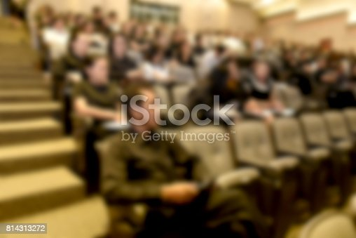 831720990istockphoto Education concept. Abstract blurred background image of education people, business people and students sitting in conference room or large hall with screen and projector for showing information. 814313272