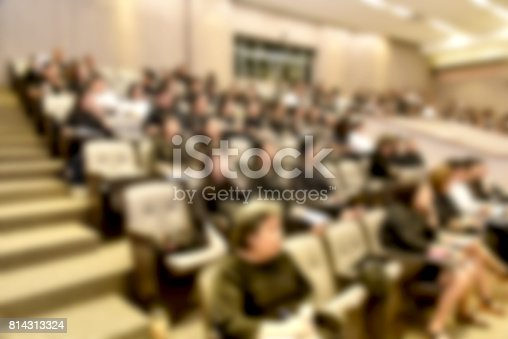 831720990istockphoto Education concept. Abstract blurred background image of education people, business people and students sitting in conference room or large hall with screen and projector for showing information. 814313324
