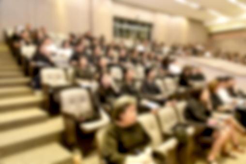 831720990 istock photo Education concept. Abstract blurred background image of education people, business people and students sitting in conference room or large hall with screen and projector for showing information. 814313324