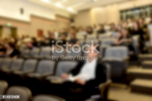 831720990istockphoto Education concept. Abstract blurred background image of education people, business people and students sitting in conference room or large hall with screen and projector for showing information. 814313406