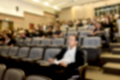 831720990 istock photo Education concept. Abstract blurred background image of education people, business people and students sitting in conference room or large hall with screen and projector for showing information. 814313406