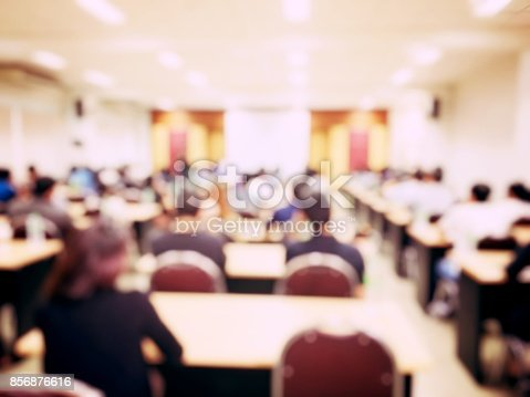 istock Education concept, blurred students and businessmen and women studying in large hall with screen and projector for showing information people teacher room presentation. 856876616