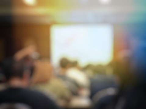 831720990 istock photo Education concept, blurred students and businessmen and women studying in large hall with screen and projector for showing information people teacher room presentation. 886570078