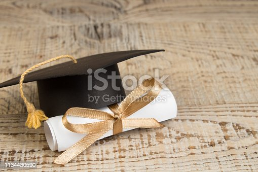 istock education concept. Graduation hat with gold tassel, scroll on the on a wooden table. Law concep- with copy space for your ad text. 1134430590