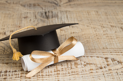 education concept. Graduation hat with gold tassel, scroll on the on a wooden table. Law concep- with copy space for your ad text