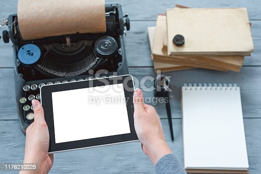 Writer with tablet computer with blank screen in hands on blue wooden desk with typewriter, books and notepad above background.