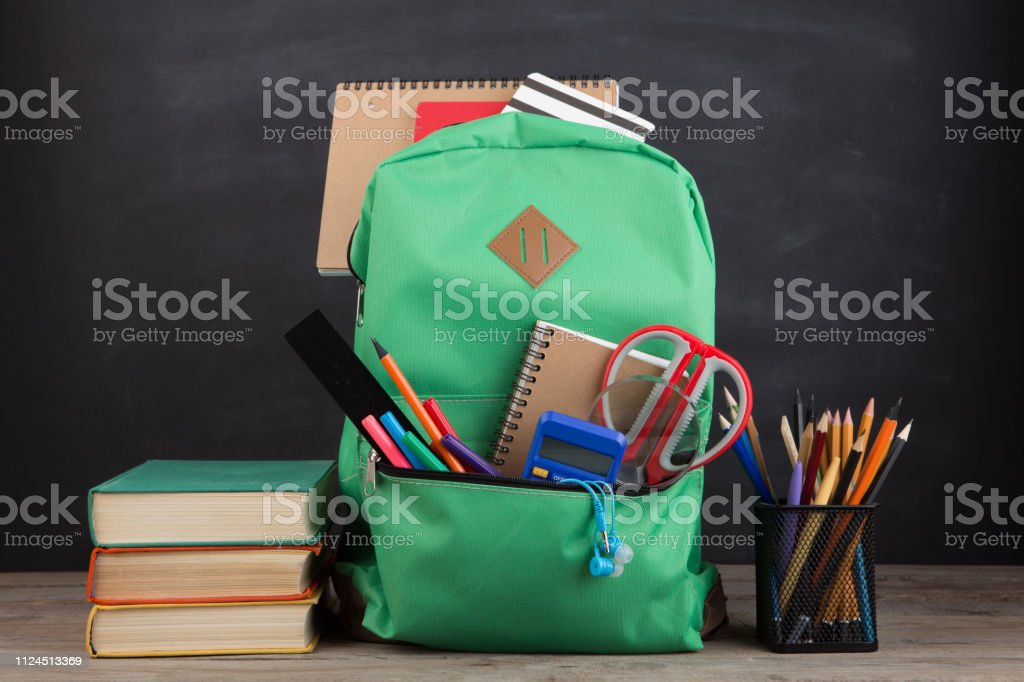 Education concept - school backpack with books and other supplies, blackboard background stock photo