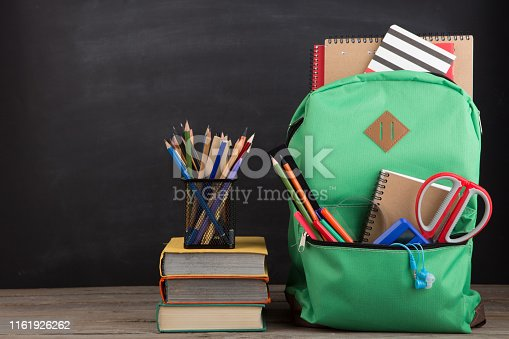 istock Education concept - school backpack with books and other supplies, blackboard background 1161926262