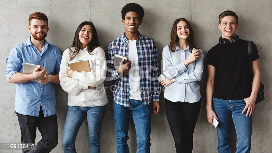 Education concept. Students smiling to camera over grey wall, having break at college
