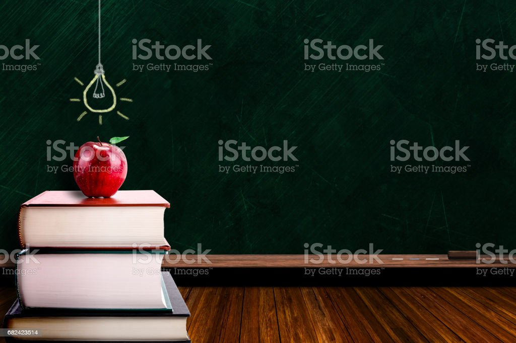 Education Concept With Apple on Books and Lightbulb on Blackboard royalty-free stock photo