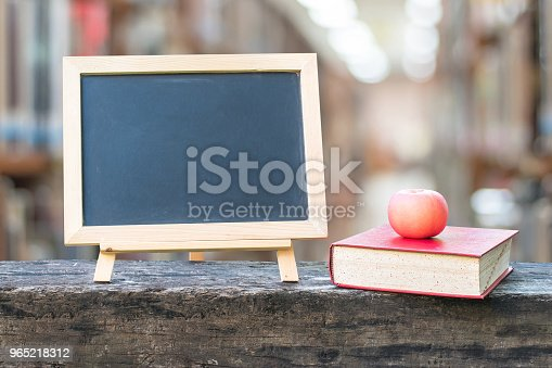 977488078 istock photo Education concept  with blank black chalkboard stand for announcement with apple, textbook on blur school college library background 965218312