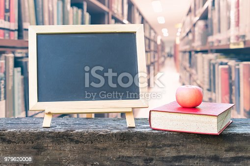 977488078 istock photo Education concept  with blank black chalkboard stand for announcement with apple, textbook on blur school college library background 979620008