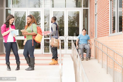 istock Education: Disabled student travels down wheelchair ramp. College campus. 528723658