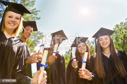 istock Education: Diverse group of friends at graduation. Cap, gowns, diplomas. 479382365