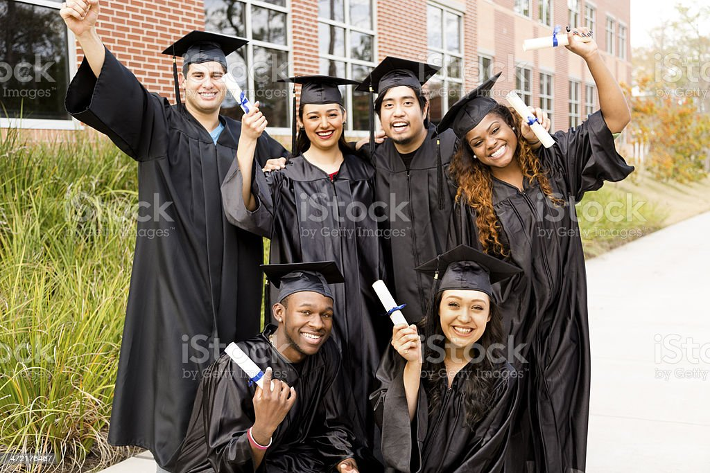 Six, multi-ethnic friends dressed in cap and gowns excitedly show off...