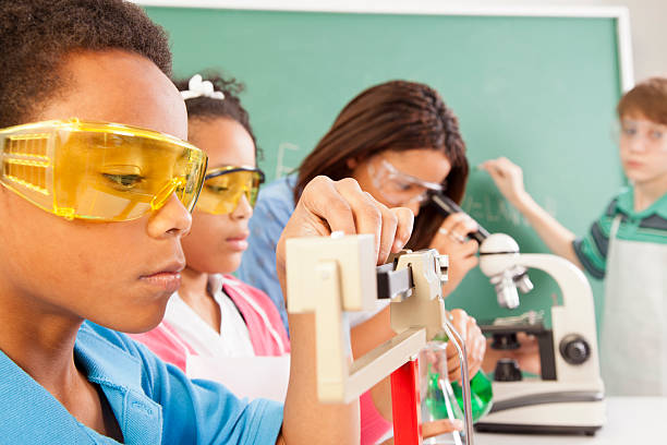 Education: Diverse students in chemistry class conducting an experiment. stock photo
