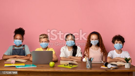 Education during virus outbreak concept. Multinational schoolkids in medical masks sitting at desk over pink background, free space. Panorama