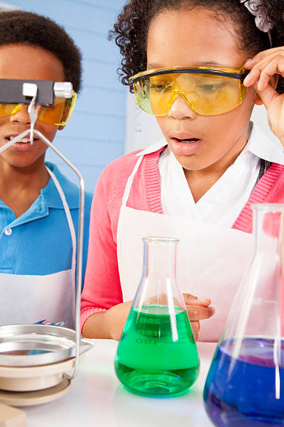 Education: Elementary students in chemistry class conducting an experiment. stock photo