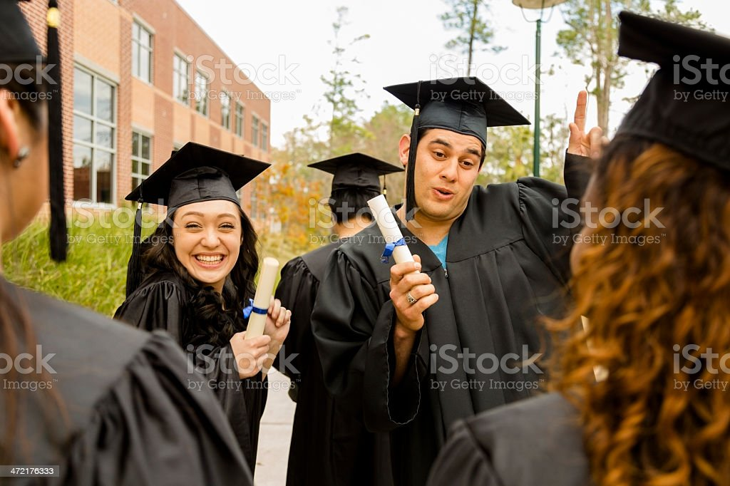 Education: Excited graduates and friends on college campus. stock photo