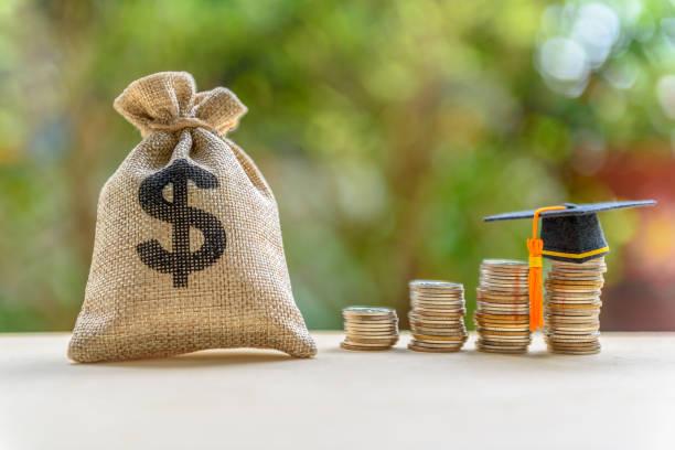 préstamo de gastos o estudiante de educación por concepto de educación post secundaria: representa a bolsa dólar, casquillo de la graduación en la fila de monedas sobre una mesa, préstamo o dinero diseñado para ayudar a los estudiantes a pagar honor - deuda fotografías e imágenes de stock