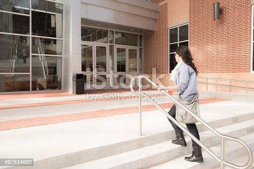 istock Education: Female college student entering school building. 497514502