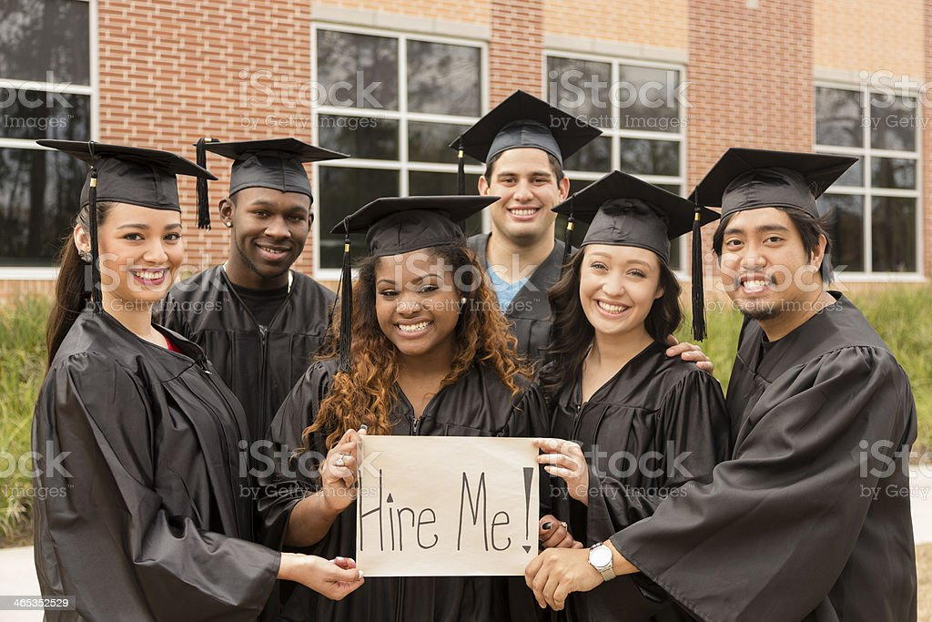 Education: Friends hold 'Hire Me' sign after college graduation. stock photo
