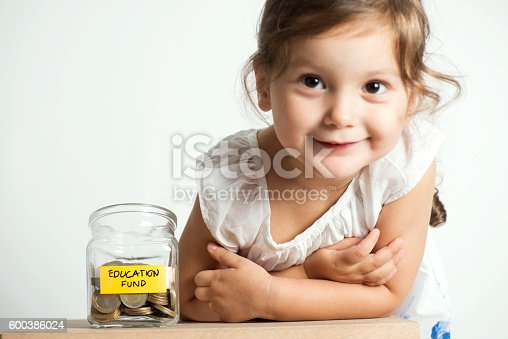 Little girl is smiling at camera beside her coin bank for her future education costs.